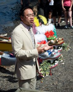 Mr Alan Seatwo 'dots the eyes' of the dragon boat head for spiritual strength and protection.