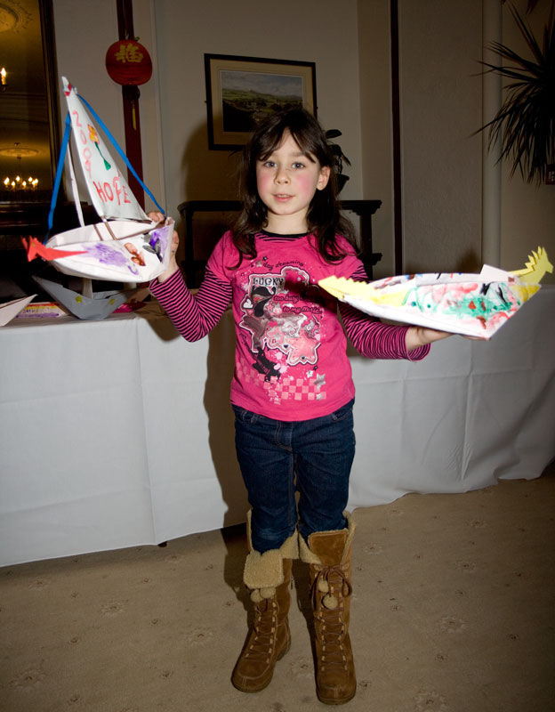 Mae-sera holds the finished paper boats.