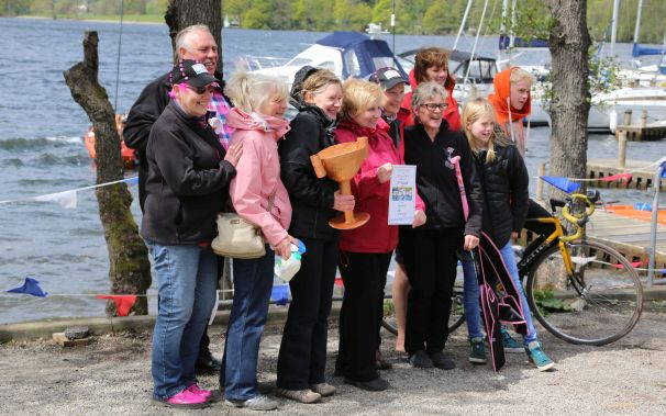 Paddlers receive the (cardboard) trophy after competing with a cardboard dragon boat.