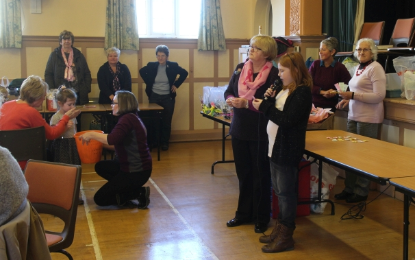 Mags, who organises this fundraiser, announces the raffle winners.