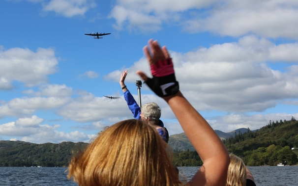 A Lancaster Bomber flies over Windermere as paddlers watch from their dragon boat.