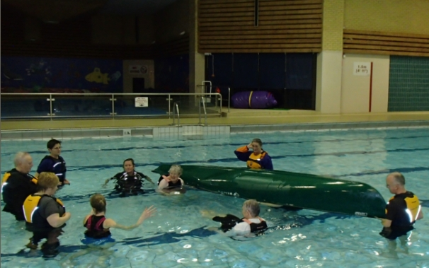Paddlers experience being under a capsized canoe.