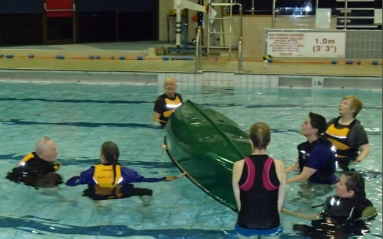 Paddlers take turns to duck under the capsized canoe.