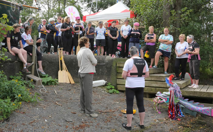 Paddlers for Life members welcomed Sylvia as they re-enacted the traditions  of Dragon Boating described by Louisa.