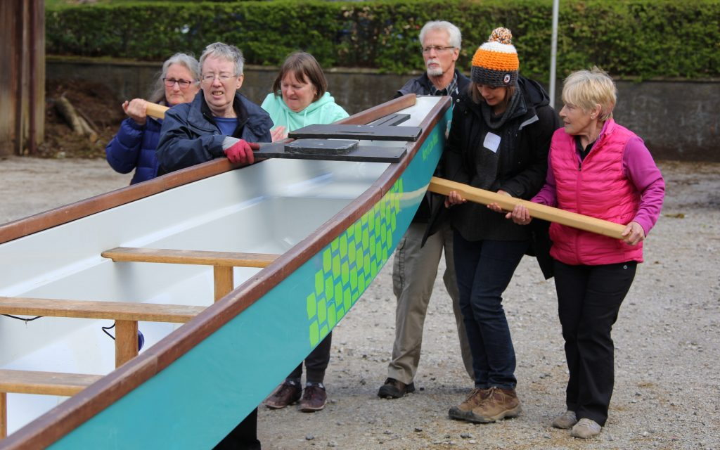 Lifting the dragon boats onto their trestles for storage.