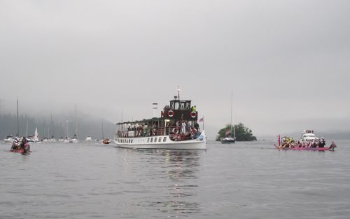 Our two dragon boats, with wet but enthusiastic crews, at each side during the 2012 Olympic Torch relay.