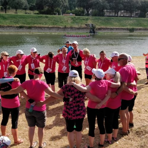 Paddlers and supporters gather together after a race on the Arno River.