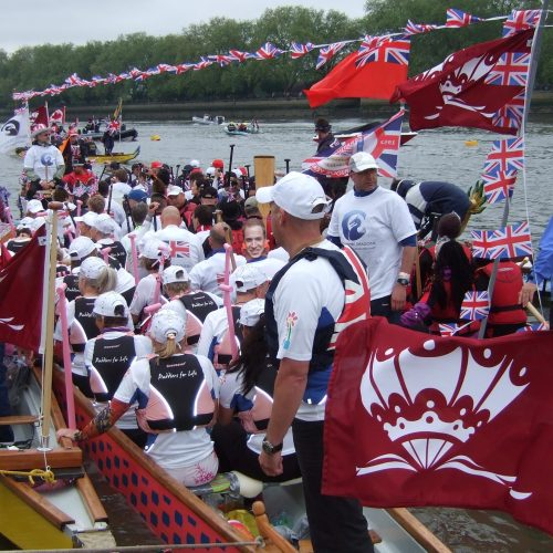 A flotilla of dragon boats assemble on the water.